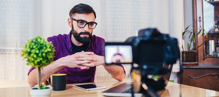 man recording at table