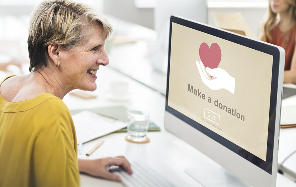 Blonde Woman smiling at donation computer screen